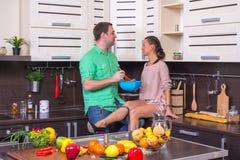 Positive Paare, die Freude bei der Stellung im k kochen und zeigen Stockfotografie