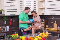 Positive Paare, die Freude bei der Stellung im k kochen und zeigen Lizenzfreies Stockbild