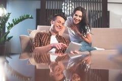 Positive Paare, die Spaß mit Gerät zu Hause haben lizenzfreie stockfotografie