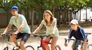 Positive parents with kid riding bicycles in park Stock Image