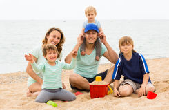 Positive parents with kids sitting at sandy beach Stock Images