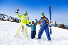 Positive parents in ski masks hold hands of son. Positive parents in ski masks hold hands of their son while standing on the snowy mountain and also holding ski Stock Photography