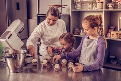 Positive pastry chef showing how to decorate cupcakes royalty free stock photo