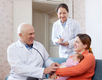 Positive pediatrician doctors examining little baby Stock Image