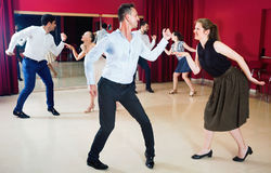 Positive people dancing twist in pairs Stock Photos