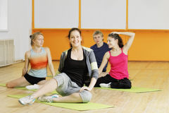 Positive people in a gym. Sitting on the floor Royalty Free Stock Photography