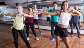 Positive people learning zumba steps. In dance hall Royalty Free Stock Images