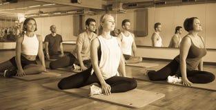 Positive people practicing yoga Stock Photos
