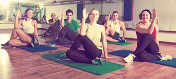 Positive people practicing yoga. Group of young cheerful people doing yoga in dance hall Royalty Free Stock Image