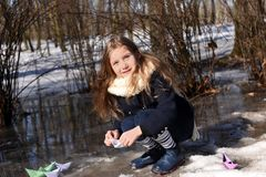 A little girl playing with paper boats in early spring semi-frozen puddles stock images