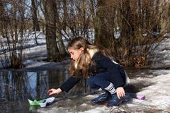 A little girl playing with paper boats in early spring semi-frozen puddles royalty free stock image