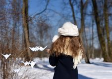 A photo representing a concept of coming spring - a smiling little girl in a park with paper cranes stock images