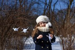 A photo representing a concept of coming spring - a smiling little girl in a park with paper cranes stock image