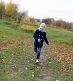 A photo of a smiling little girl running on a path in an autumn park stock photos