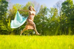 Positive Portrait of Smiling Caucasian Woman Running Barefoot Oudoors With Flying Kerchief. Shoot From Low Angle royalty free stock images