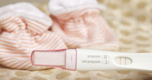 Positive Pregnancy Test and Baby Booties. On a Dotted Background royalty free stock photo