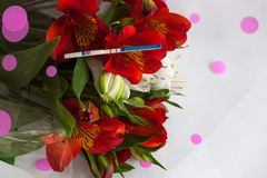 Positive pregnancy test with a bouquet of alstroemeria flowers stock image