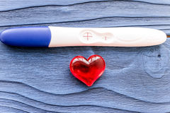 Positive pregnancy test with heart on wooden background top view stock image