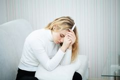 Positive pregnancy test. Young woman feeling depressed and sad a stock photo