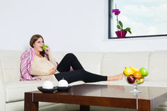 Positive pregnant woman eating green apple. On sofa Stock Photo