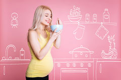 Positive pregnant woman eating in the kiitchen Stock Photos