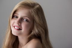 Positive pretty child is expressing gladness. Feeling glee. Close-up of face of happy adorable little girl with naked shoulders is standing and looking at camera royalty free stock photos