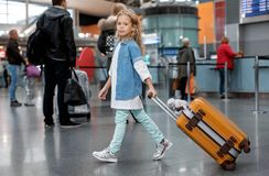 Positive pretty child is holding her baggage stock images