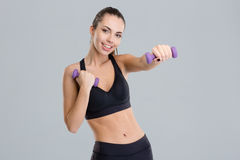 Positive pretty fitness girl exercising with dumbbells Stock Photo