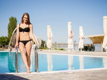 Positive, pretty girl in a bikini walking on a swimming pool background. Resort concept. Copy space. Royalty Free Stock Photography