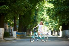 Positive pretty girl in white dress and straw hat is happy riding blue bike down wide beautiful park alley royalty free stock image