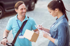 Positive professional courier delivering the parcel. Like my work. Positive bearded professional courier holding the parcel and delivering it while smiling royalty free stock images