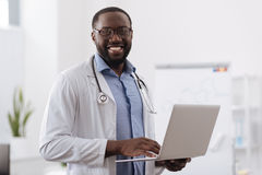 Positive professional doctor working on the laptop. Modern medicine. Positive professional handsome doctor holding a laptop and smiling while working on it Royalty Free Stock Photos