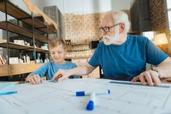 Positive professional engineer helping his grandson. Sharing experience. Positive professional smart engineer sitting together with his grandson and helping him Royalty Free Stock Photos