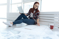 Positive professional engineer holding a pencil. Working drawing. Positive professional nice engineer holding a pencil and drawing a line while working on the Stock Image