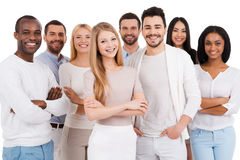 Positive professional team. Group of positive and diverse people in smart casual wear looking at camera and smiling while standing against white background Royalty Free Stock Photo
