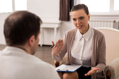 Positive professional therapist giving advice. Dealing with problems. Positive professional female therapist holding a pen and looking at her patient while Stock Photo