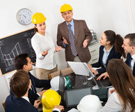 Positive professionals with laptops and helmets having working m. Successful positive professionals with laptops and helmets having working meeting Royalty Free Stock Image
