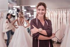 Positive professionelle weibliche Damenschneiderin, die zu Ihnen lächelt stockfotografie