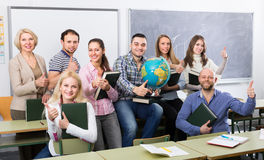 Positive professor and group of students. Female professor and cheerful students posing in classroom at extension courses Royalty Free Stock Images