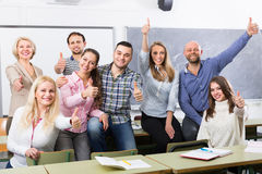 Positive professor and group of students. Smiling professor and cheerful students posing in classroom at extension courses Stock Image