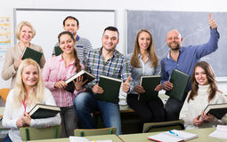 Positive professor and group of students. Smiling female professor and cheerful students posing in classroom at extension courses Stock Photo