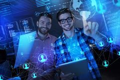 Positive programmers feeling glad while working with transparent screen. Cheerful team. Excited young clever programmers smiling while standing in front of a Royalty Free Stock Photo
