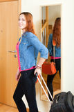 Positive red-haired woman with luggage in home going on holiday. Positive red-haired woman with luggage near door going on holiday Stock Images
