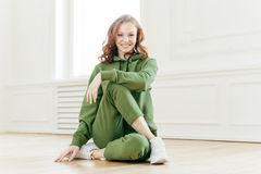 Positive redhead fitness girl feels relaxed, wears tracksuit, sportshoes, has rest after yoga training indoor, poses on floor, royalty free stock photo