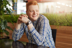 A positive redhead hipster with freckles wearing stylish checked shirt and watch sitting at wooden table in cosy restaurant having Royalty Free Stock Photo