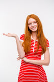 Positive redhead young woman holding copyspace on the palm Stock Photos