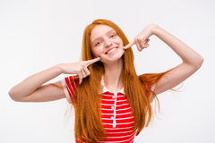 Positive redhead young woman touching her cheeks with fingers Stock Photos