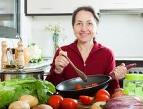 Positive reife Frau, die mit Bratpfanne kocht stockfotografie