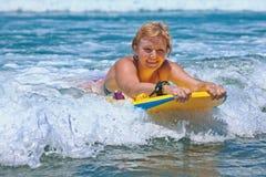 Positive reife Frau, die mit Spaß auf Meereswogen surft stockfotos