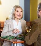 Positive reife Paare, die im Restaurant und in der Unterhaltung zu Abend essen Stockfotos